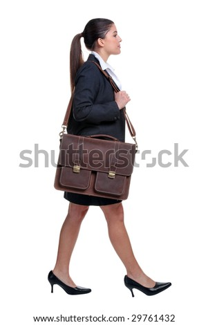 Businesswoman walking with briefcase over her shoulder, isolated on white background. - stock photo