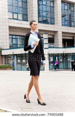 businesswoman walking with file in heads, outdoor - stock photo