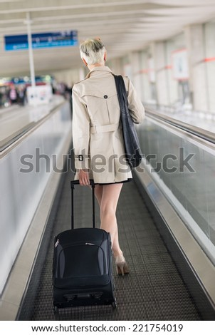 Businesswoman walking with trolley on tradmill at Charles de Gaulle airport, Paris.