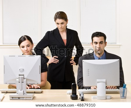 Businesswoman watching co-workers work - stock photo