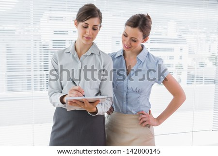 Businesswoman watching her colleague write on clipboard standing in their office - stock photo