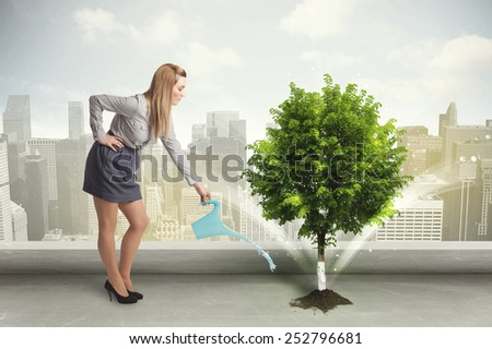 Businesswoman watering green tree on city background concept - stock photo
