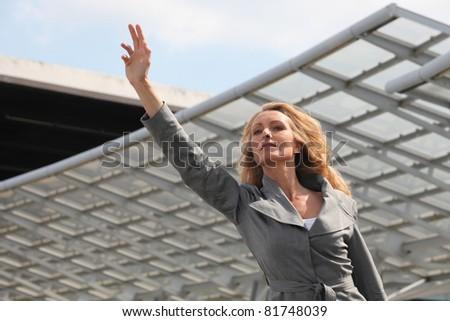 Businesswoman waving taxi - stock photo