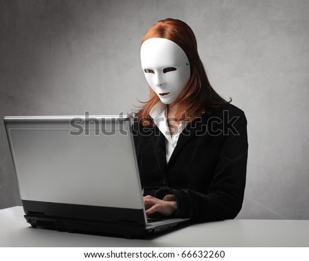 Businesswoman wearing a mask and using a laptop - stock photo