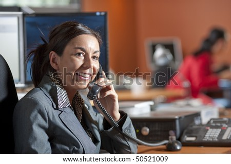 Businesswoman wearing a suit is smiling while talking on the telephone in an office environment. Horizontal shot - stock photo