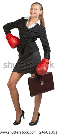 Businesswoman wearing boxing gloves holding briefcase, standing akimbo, looking at camera, smiling Isolated over white background