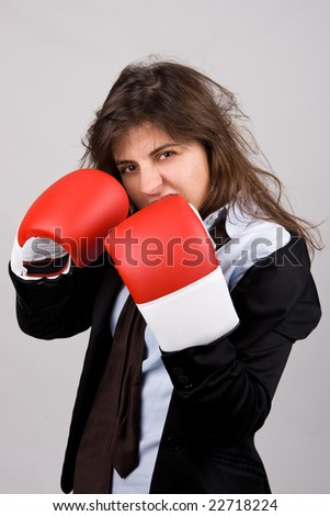 businesswoman wearing boxing gloves with confident attitude. grey background.