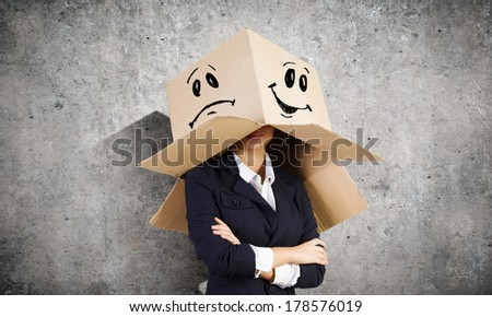 Businesswoman wearing carton box with drawn smiley on head - stock photo
