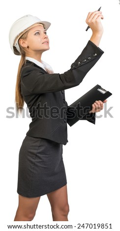 Businesswoman wearing hard hat, holding clipboard, drawing or writing something up in the air. Isolated over white background - stock photo