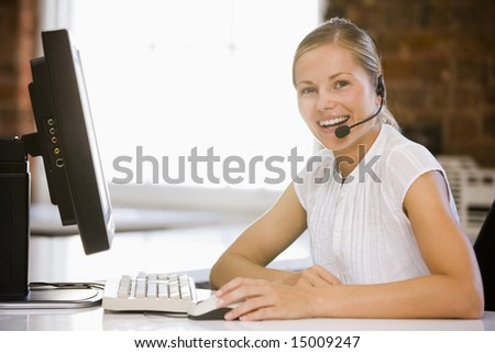 Businesswoman wearing headset sitting in office smiling - stock photo