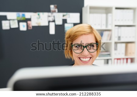 Businesswoman wearing heavy framed glasses sitting behind her monitor looking up with a beaming smile as she listens to someone off frame - stock photo