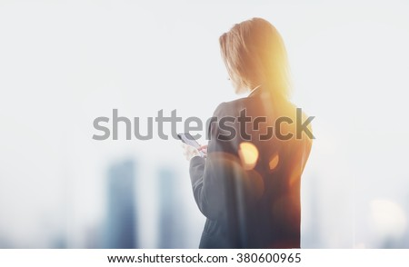 Businesswoman wearing modern suit and touching screen of her smartphone. City blurred background - stock photo