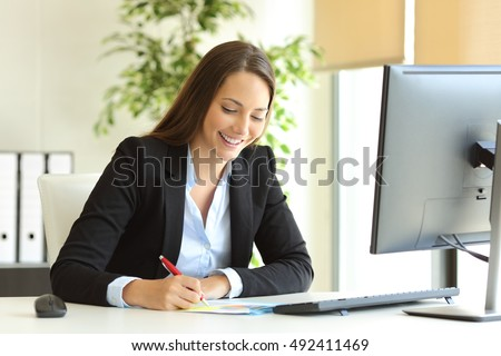 Businesswoman wearing suit working handwriting notes in a desktop at office