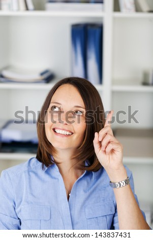 Businesswoman with a bright idea and a broad smile on her face raising her finger as she suddenly realizes the solution to a problem - stock photo