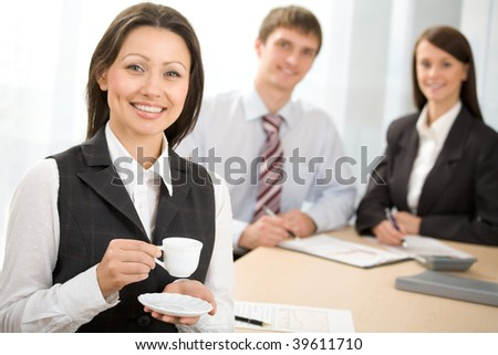 Businesswoman with a coffee cup in the office - stock photo