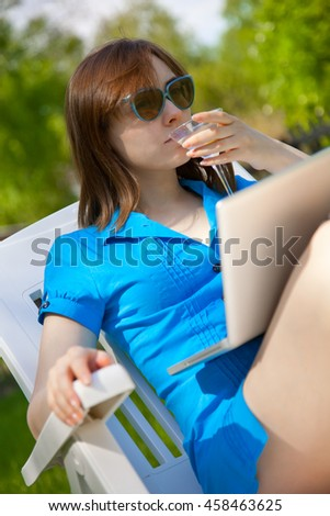 Businesswoman with a glass of martini looking to the laptop outdoors - stock photo