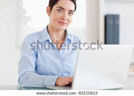 Businesswoman with a laptop looking at the camera in an office - stock photo