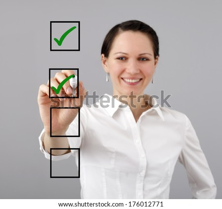 Businesswoman with a marker and check list - stock photo