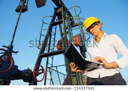 Businesswoman with a notebook in an oilfield - stock photo