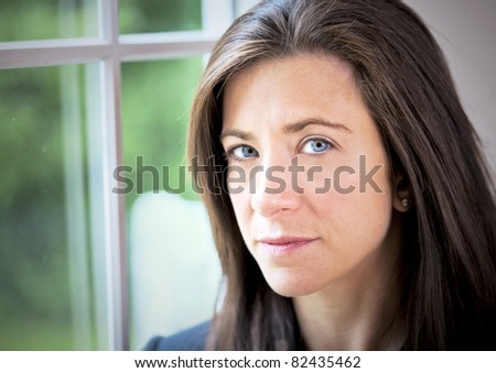 Businesswoman with a serious expression standing by window - stock photo