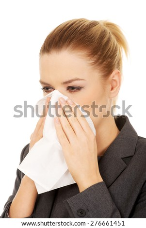 Businesswoman with an allergy sneezing into tissue.