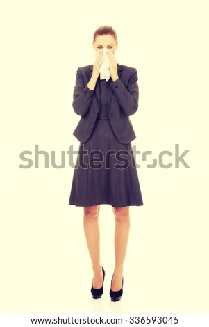 Businesswoman with an allergy sneezing into tissue. - stock photo
