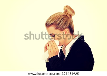 Businesswoman with an allergy sneezing into tissue - stock photo