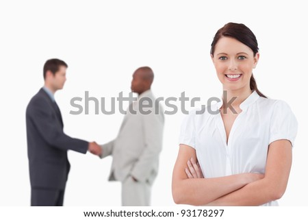 Businesswoman with arms folded and hand shaking trading partners behind her against a white background