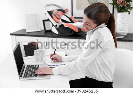 Businesswoman with baby boy working from home using laptop and mobile phone - stock photo