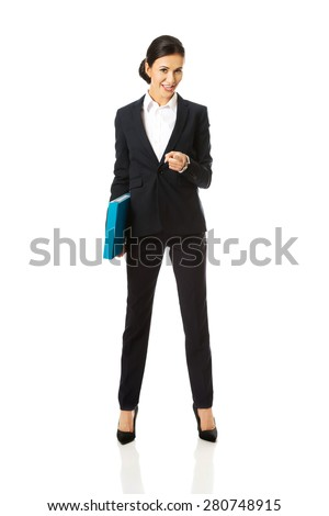 Businesswoman with binder pointing on you. - stock photo