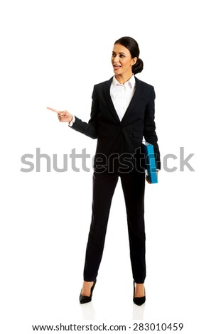 Businesswoman with binder pointing to the left. - stock photo