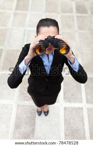 businesswoman with binocular standing outdoor, top view - stock photo
