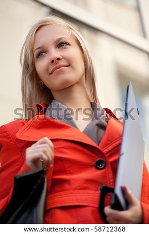 Businesswoman with blue folder outdoors