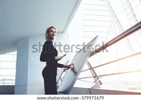 Businesswoman with cell telephone in hand touching big computer monitor while standing in modern office interior, young female looking away while verify data on mobile phone and interactive display - stock photo