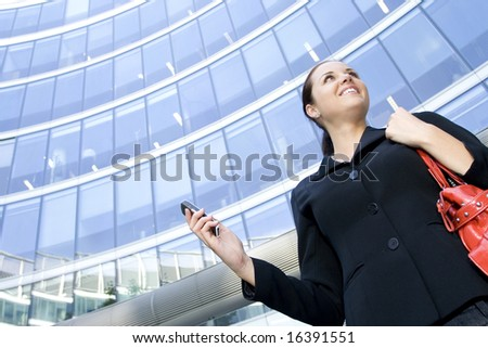 Businesswoman with cellphone by skyscraper - stock photo