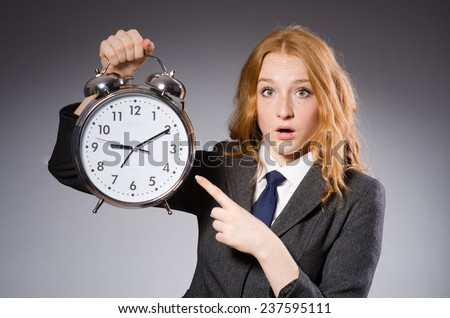 Businesswoman with clock being late for her deliverables - stock photo