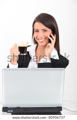 Businesswoman with coffee and mobile telephone - stock photo