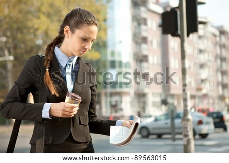 businesswoman with coffee reading newspaper, standing on street - stock photo