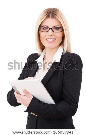 Businesswoman with digital tablet. Confident mature businesswoman working on digital tablet and smiling while standing isolated on white - stock photo