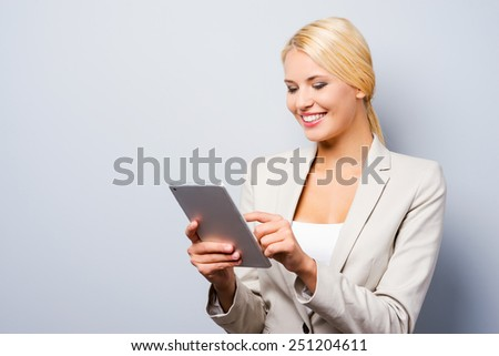 Businesswoman with digital tablet. Confident young businesswoman working on digital tablet and smiling while standing against grey background - stock photo