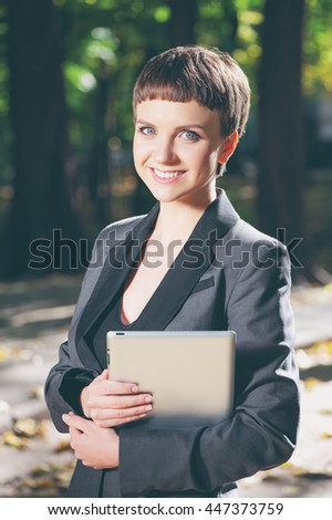Businesswoman with digital tablet. Confident young caucasian woman in formalwear holding digital tablet and smiling while standing at park outdoor - stock photo