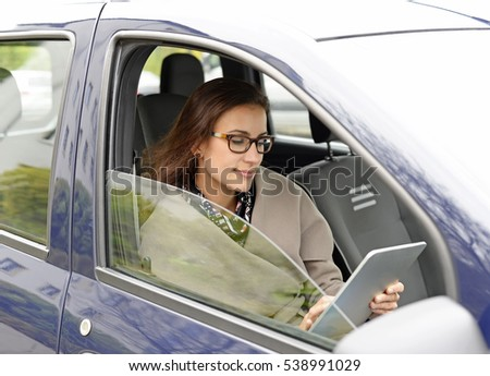 businesswoman with digital tablet in the car