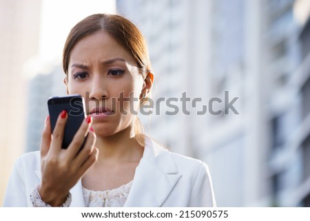 Businesswoman with disappointed expression using mobile phone in city street, receiving bad news via email - stock photo