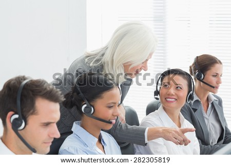 Businesswoman with executives using computers in office - stock photo