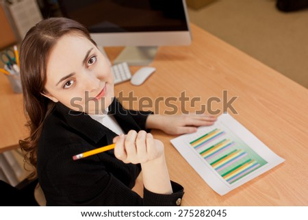 Businesswoman with financial report at office - stock photo
