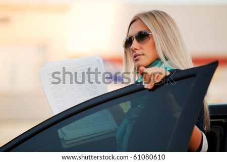 Businesswoman with financial reports sitting in a car. - stock photo