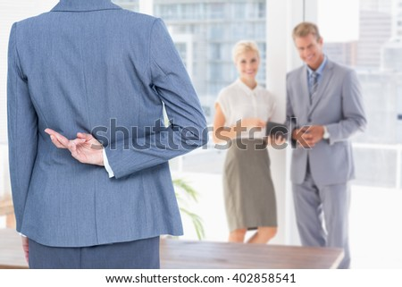 Businesswoman with fingers crossed behind her back against smiling business partners looking at camera - stock photo
