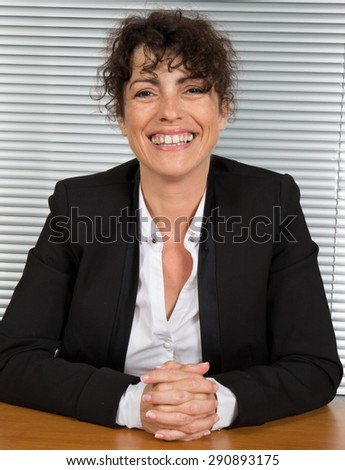 Businesswoman with fingers crossed sitting at the desk and looking at camera