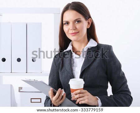 Businesswoman with folders and cup of coffee, standing in office - stock photo