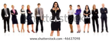 businesswoman with glasses pointing with her team behind her